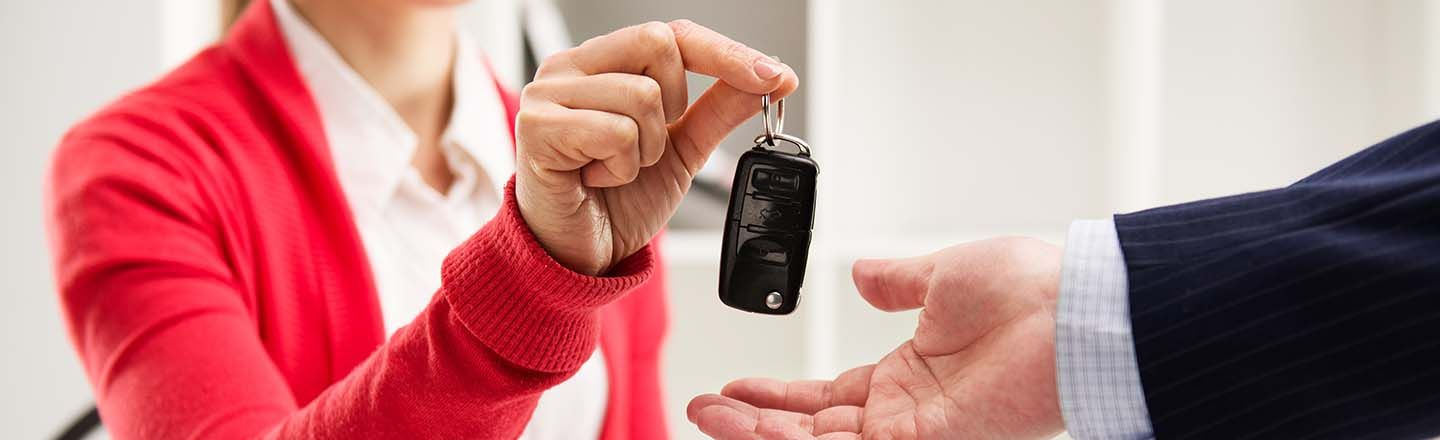 Woman employee at dealership handing male customer car keys