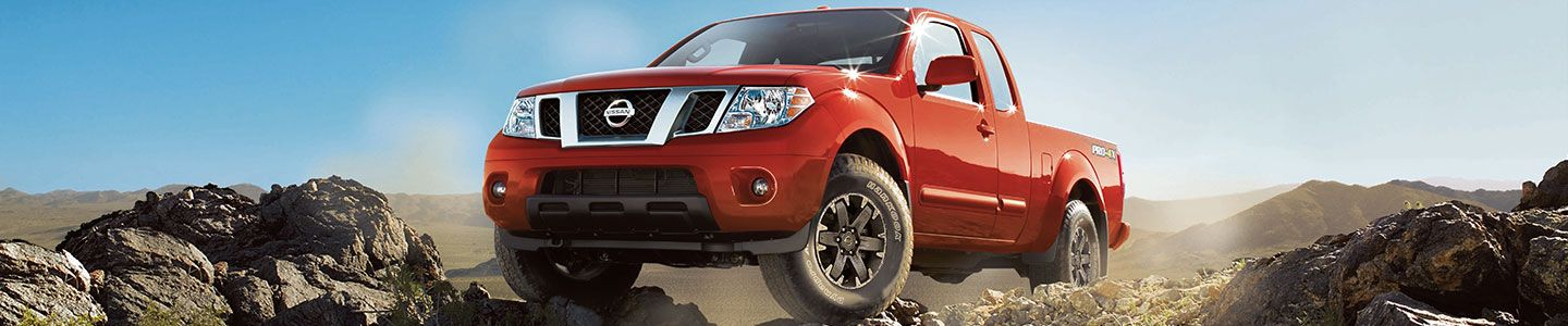 Red Nissan Frontier on rocky terrain, blue sky