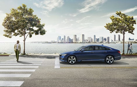 Blue 2021 Honda Accord stopped at pedestrians crosswalk city skyline in the background