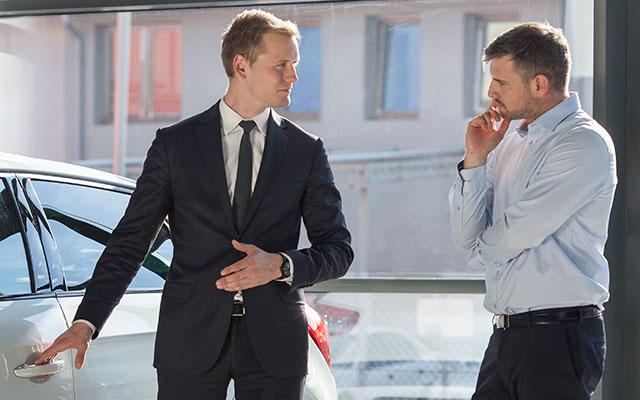 Salesman explaining car to discerning customer