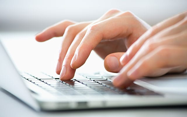 Close up of hands typing on keyboard