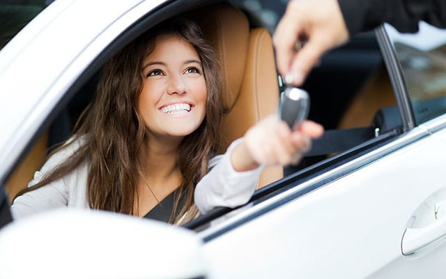 Smiling young woman in driver's seat receiving keys to her new car