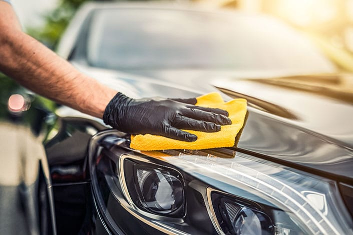 Gloved hand detailing the front of a sedan