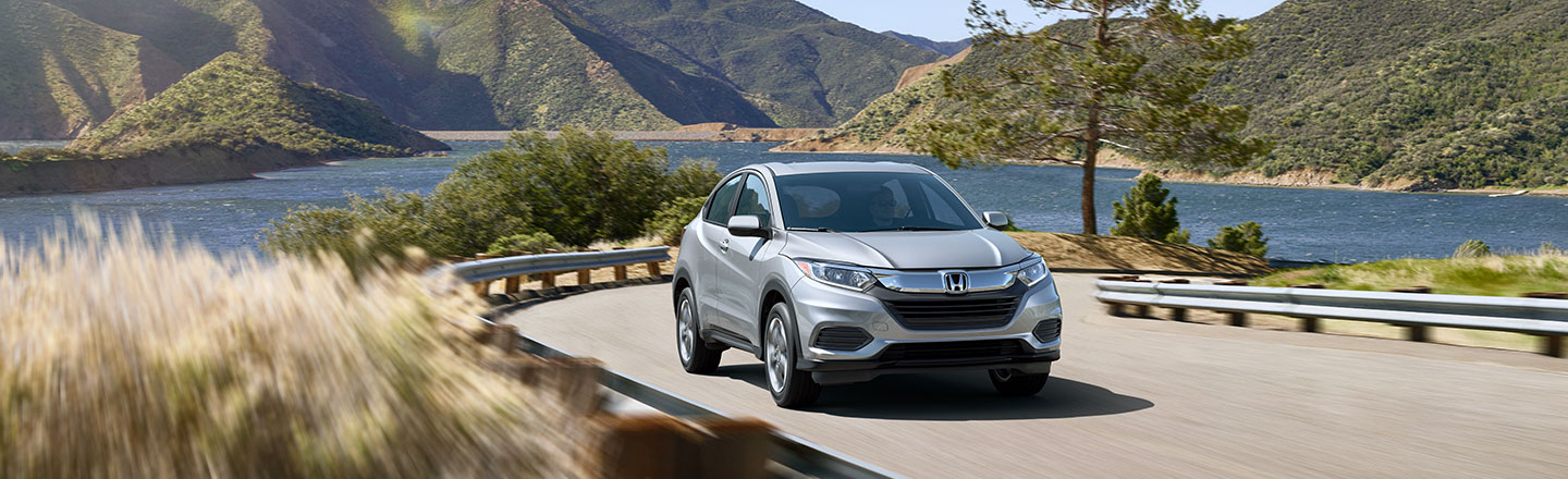 Honda HR-V driving along scenic highway with lake and mountains in background
