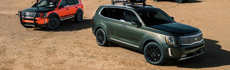 Two Kia Tellurides parked on dirt