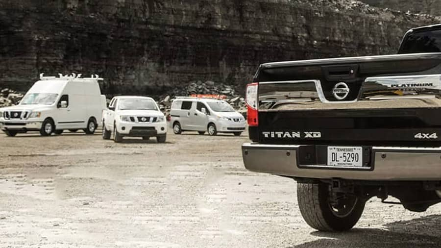 Four Nissan commercial vehicles parked in a rock quarry