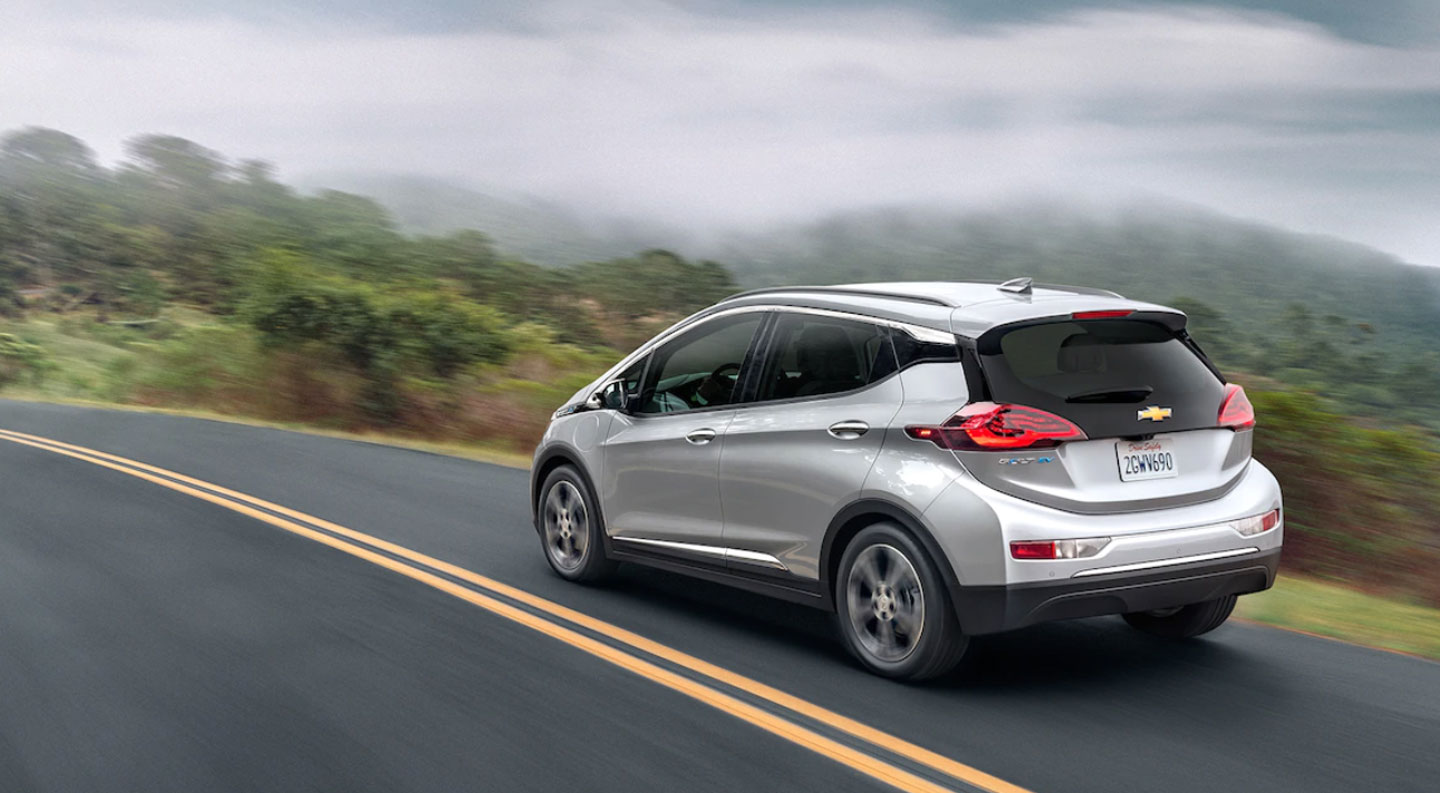 silver 2020 Chevy Bolt EV driving passed forest
