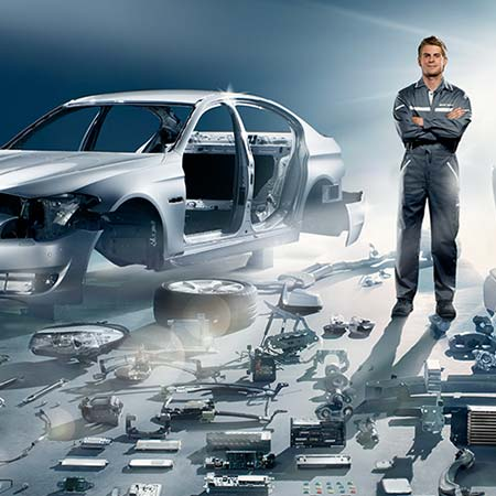 Technician standing amongst laid out parts at a BMW service center at BMW of El Cajon