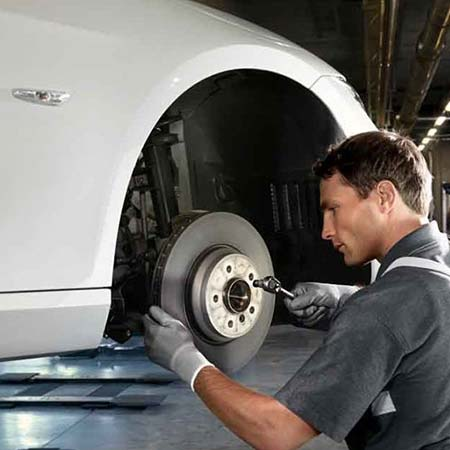 Technician working on brakes at a BMW service center in El Cajon