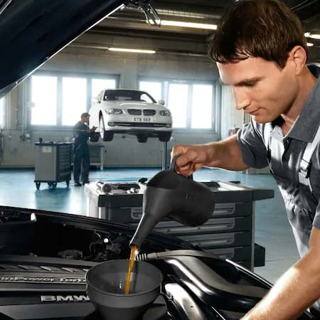 Technician pouring engine oil in engine at a BMW service center near San Diego