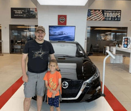 dad and son in front of black Nissan Altima