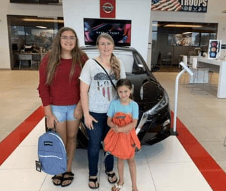 mother with daughters with new backpacks