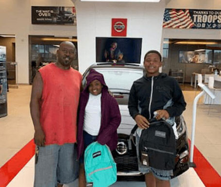 father and 2 kids with new backpacks