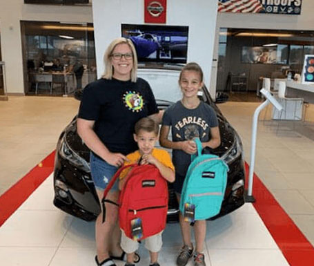 mother and 2 kids with new backpacks