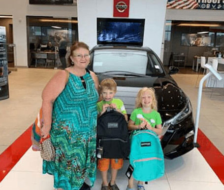 woman and 2 small children with new backpacks