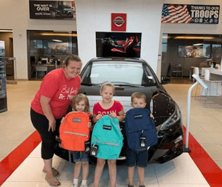 woman with 3 small children with new backpacks