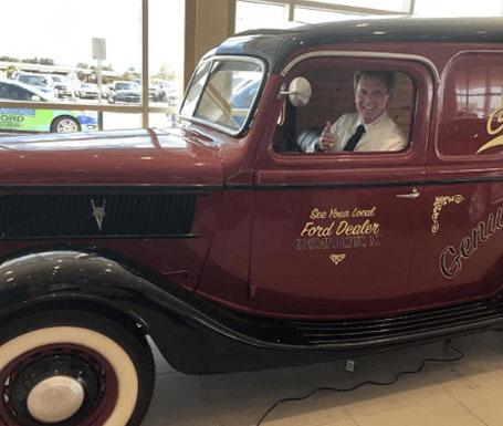 man in maroon vintage car