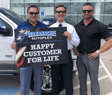 men standing holding a happy customer sign