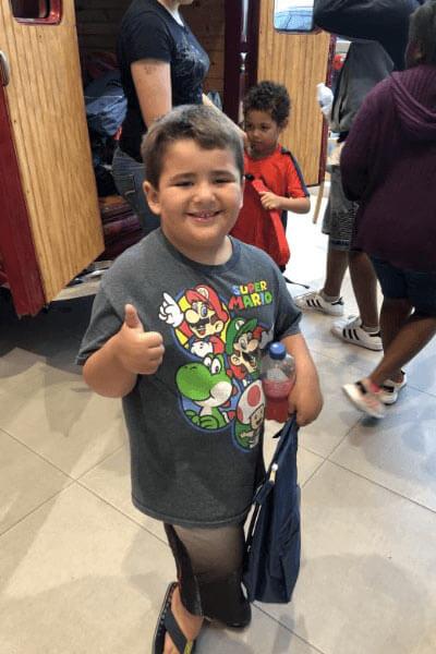 happy boy wearing mario kart shirt