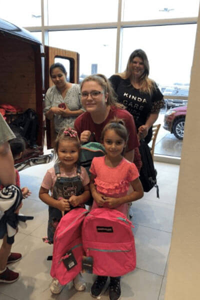3 women and 2 small girls with new backpacks