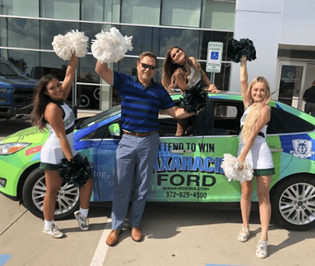 cheerleaders and man in front of car