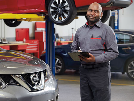 Certified Nissan Service Technician with clipboard