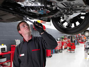 Certified Nissan Service Technician repairing the bottom of a commercial vehicle