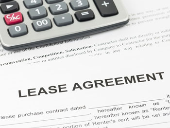 Vehicle lease agreement positioned next to a calculator