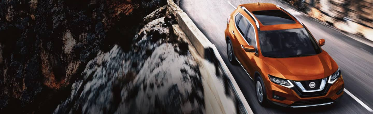 The 2020 Nissan Rogue in orange driving along a mountain