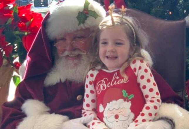 Santa and little girl in polka dot pj's