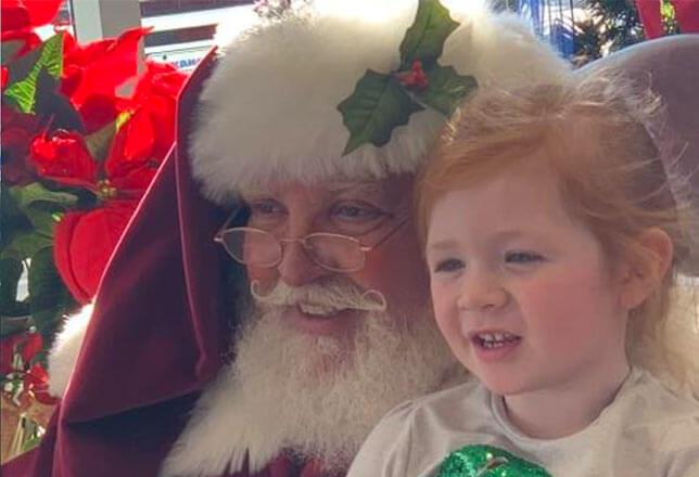 Santa and cute redhead little girl