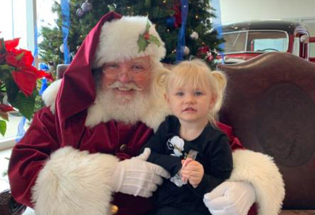 Santa and little blonde girl with pig tails