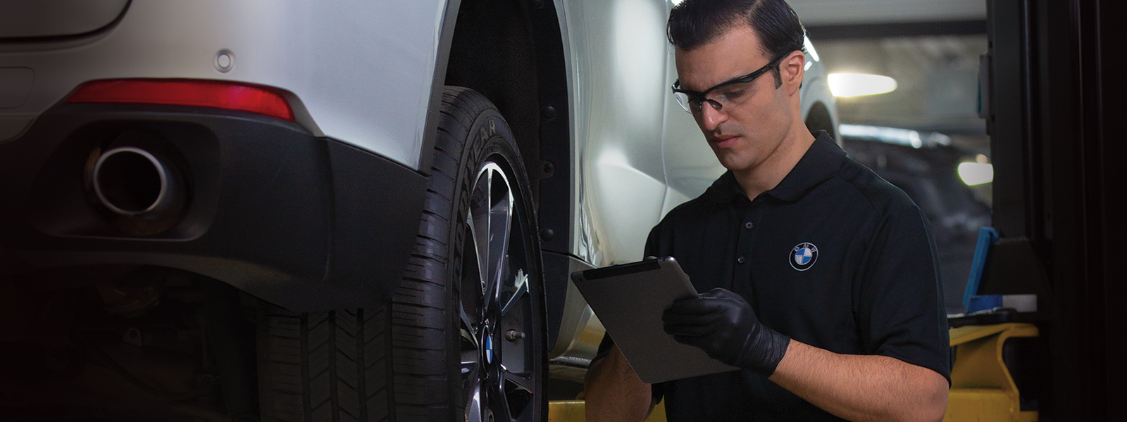 BMW Service Technician in service bay inspecting a BMW on a lift. BMW oil changes available now at BMW of El Cajon's value service center