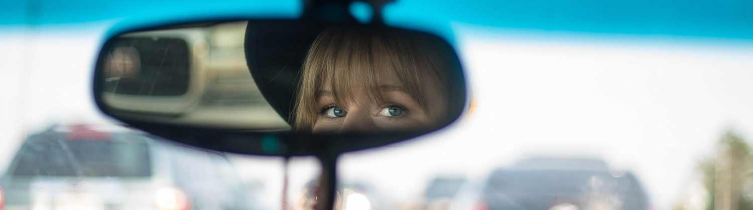 A teenage driver looks in a rearview mirror