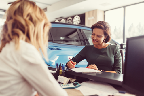 Woman in dealership signing lease papers