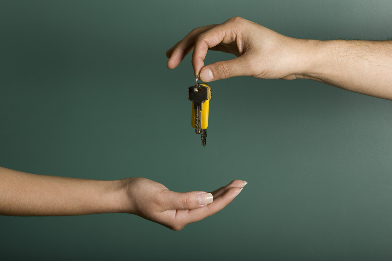 Hand holding keys dropping into another person's hand in front of a deep green background