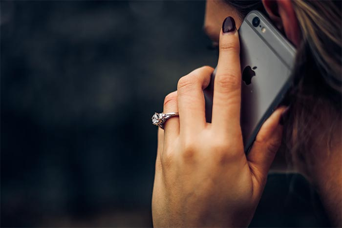 a photo showing a woman holding a mobile phone up to her ear
