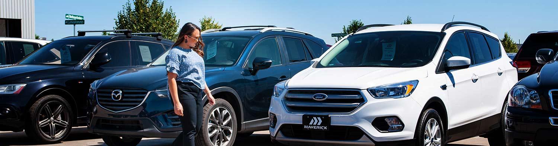 A women walks along a row of cars at a dealership