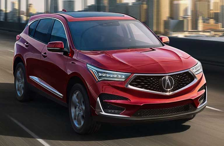 Driver angle of a silver 2019 Acura RDX driving down a city road