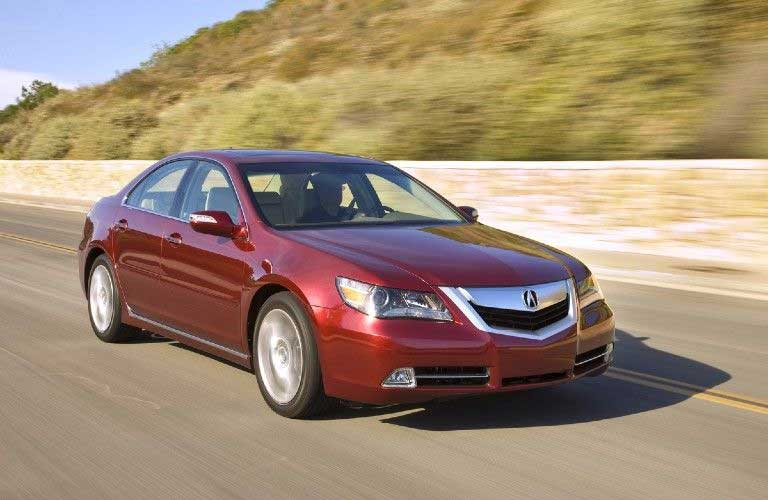 Front passenger angle of a red 2009 Acura RL driving on a road