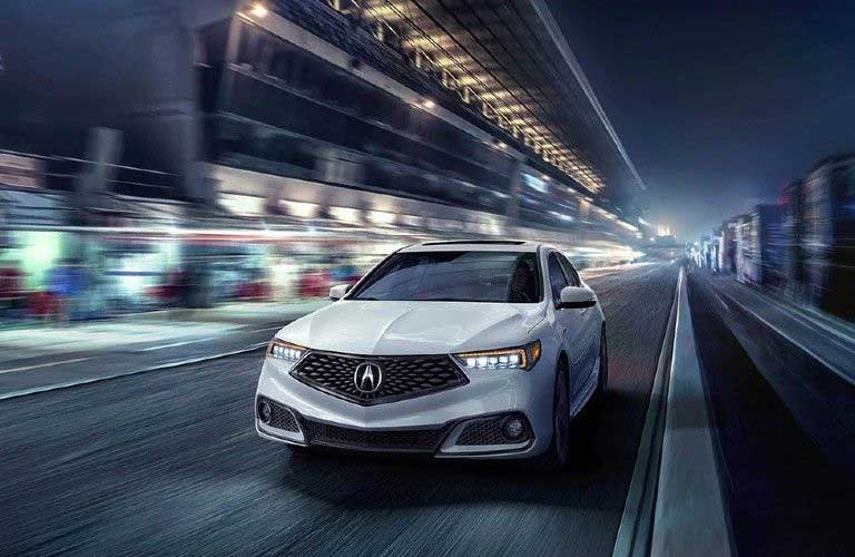 Front driver angle of a white 2020 Acura TLX driving at night