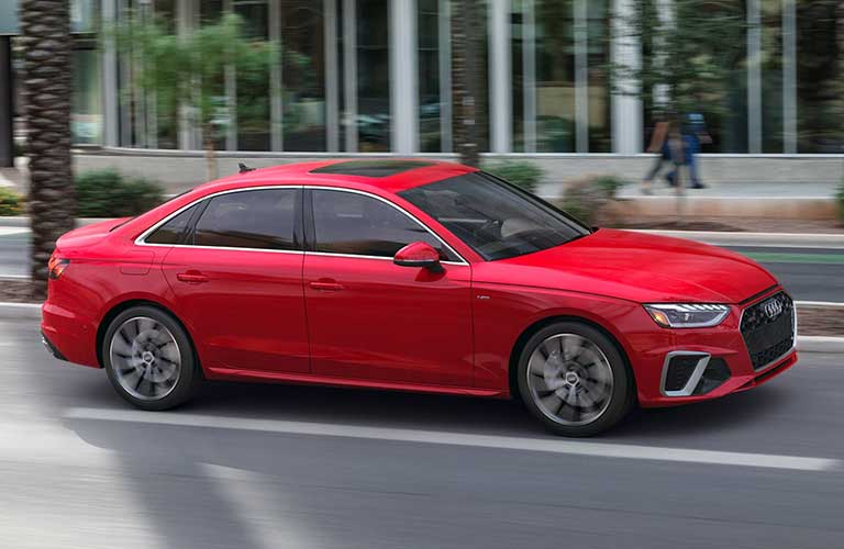 Front passenger angle of a red 2021 Audi A4 driving in a city
