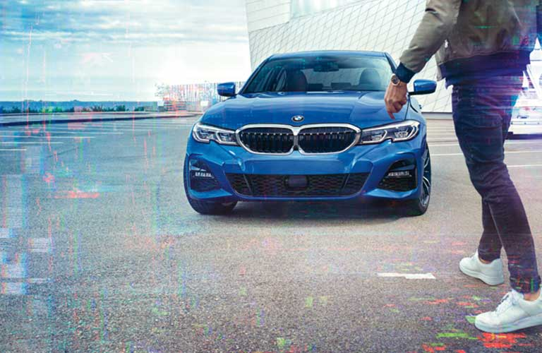 Front angle of a blue 2019 BMW 3 Series with a person walking in front