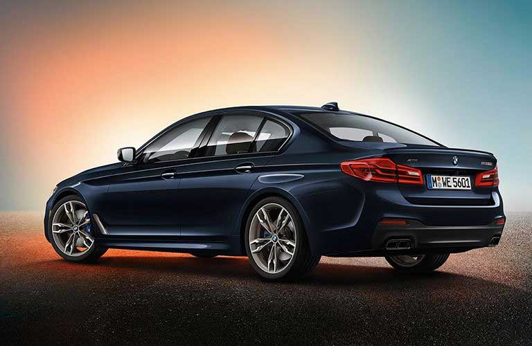 Rear driver angle of a blue 2019 BMW 5 Series with sunset colors in the background