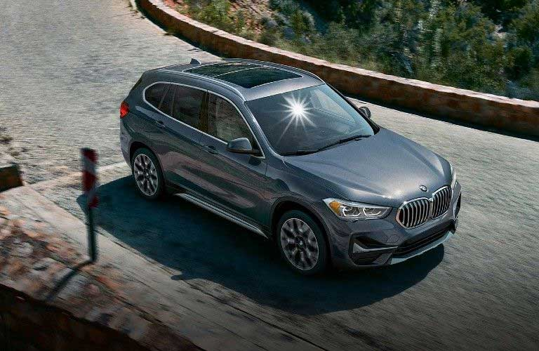 Front passenger angle of a grey 2020 BMW X1 driving on a road
