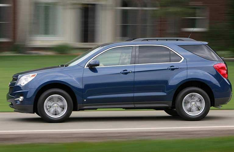 2016 Chevrolet Equinox driving by houses on a road