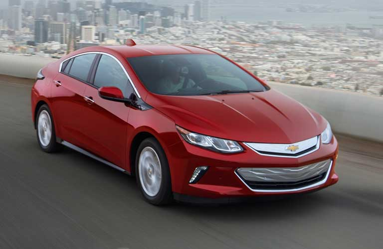 Front passenger angle of a red 2019 Chevrolet Volt driving away from a city