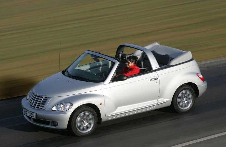 Front driver angle of a silver 2006 Chrysler PT Cruiser convertible driving on a road