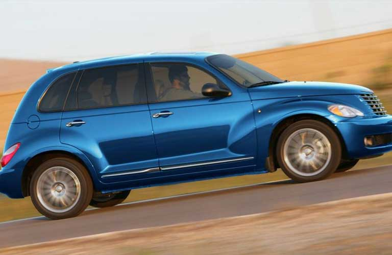 Passenger angle of a blue 2010 Chrysler PT Cruiser driving on a road