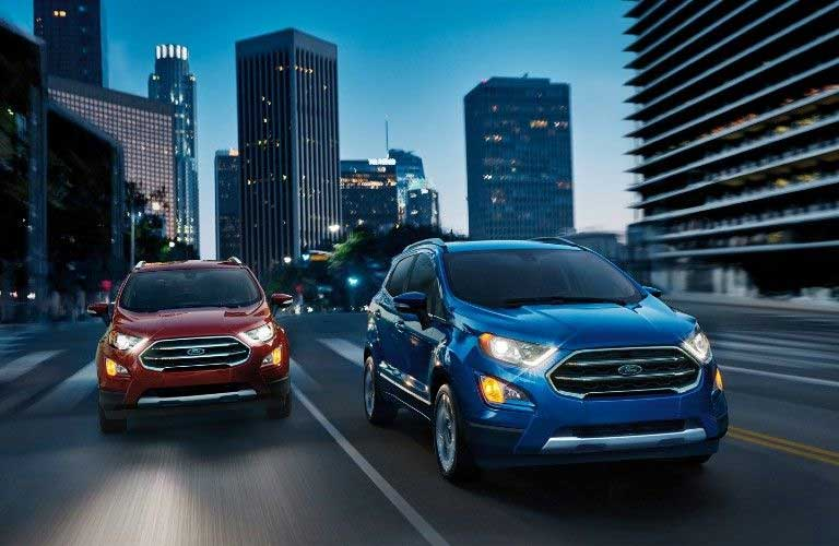 A blue 2020 Ford EcoSport driving next to a red 2020 Ford EcoSport in a city
